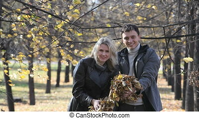 Feeling autumn - Adorable couple having fun throwing...