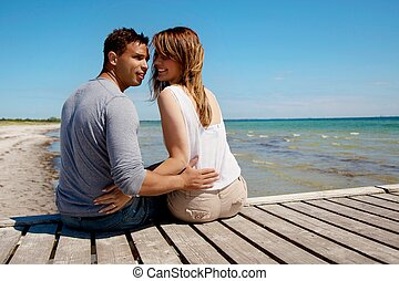 Attractive Couple Sitting on a Pier