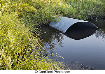 irrigation ditch with culvert - green meadow and irrigation...