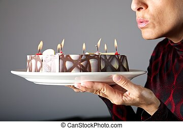 blowing out small candles on cake - adult woman hands...