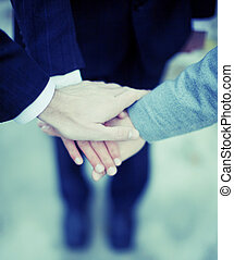 team - close-up of three businessmens hands on top of each...