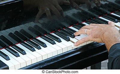 hand of a pianist that plays the white and black keys on...