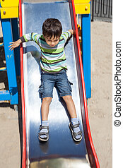 playground - Cute boy playing on slide