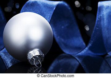 dull silver christmas ball in front of a blue ribbon on black reflective background