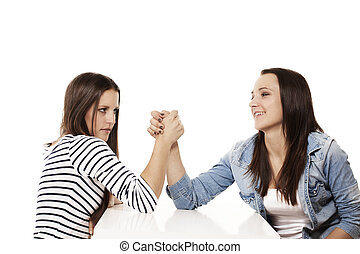 one happy and one strained teenager arm wrestling on white...