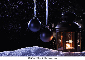 burning lantern at night with two hanging blue christmas...