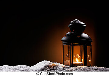burning black vintage christmas lantern in the night on snow
