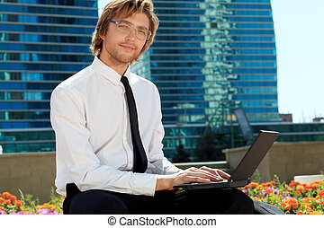 big city - Young businessman working with laptop in the big...