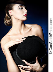 shoulders - Elegant naked young woman posing with black pot...