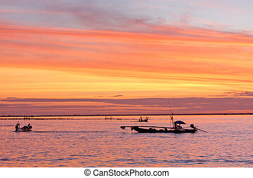 fishermen with yellow and orange sun in the background