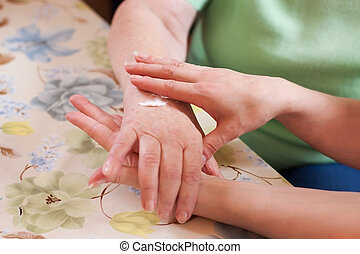 Geriatric nurse anoints elderly womans hand - Nurse cares...