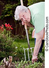 Pensioner chops weeds in the garden