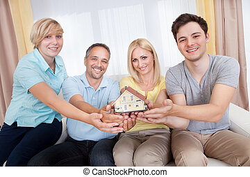 Happy family holding a model house