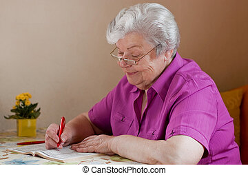 Senior puzzles with the help of reading glasses - pensioner...