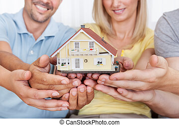 Happy family holding a model house - Happy parents with...