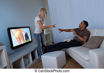 Wife preventing man watching female TV - Wife standing...