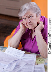 Elderly woman sits in front of papers and desperate -...