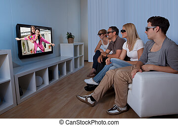 Family watching 3D television - Family with teenage children...
