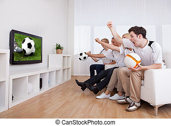 Jubilant family watching television as they cheer on their...