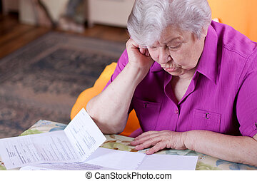 Senior reads papers and works hard - Pensioner read...
