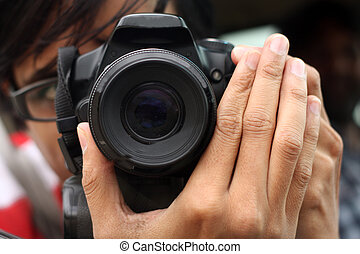 Photographer - A photographer focussing the lens on his...