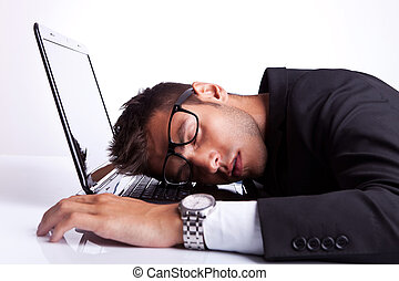 Business man sleeping on a laptop computer on gray...