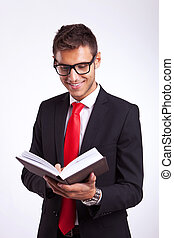 young man in a suit reading an interesting book