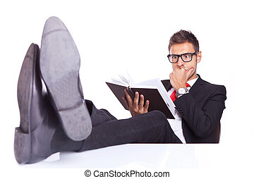 business man reading a thriller book - business man at his...