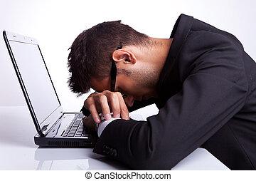 Tired business man sleeping on laptop
