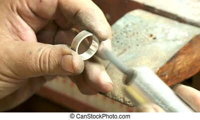 Goldsmith polishing an ring