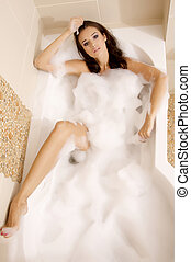Attractive brunette woman in bath relaxing. Closeup of young...