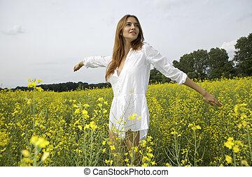 brunette woman in a yellow flowers field