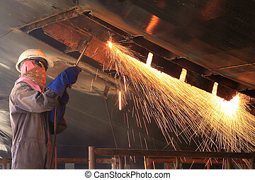 a welder working a torch at shipyard