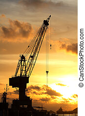 Cranes in dockside at sunset