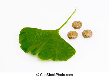 Healthy - Ginkgo biloba leaf with pills on bright background...