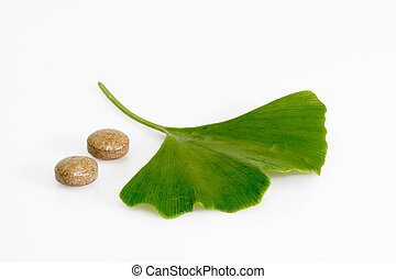 Medical therapy - Ginkgo biloba leaf with pills on bright...