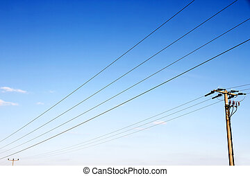 Power lines in front of a blue sky.