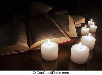 open books and candles on wood table