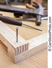 hammer and nail in wood table construction background
