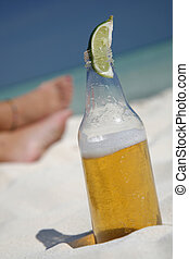 Beer and Feet on the Beach - Beer with lime wedge on the...
