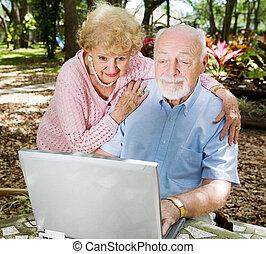 Computer Savvy Seniors - Senior couple enjoys using their...
