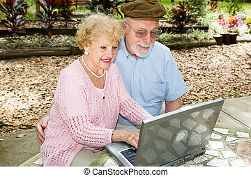 Seniors Computing Outdoors - Senior couple outdoors on their...