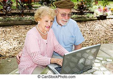 Seniors Computing Outdoors - Senior couple outdoors on their...