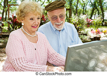 Seniors Enjoy Computer - Happy senior couple on their laptop...
