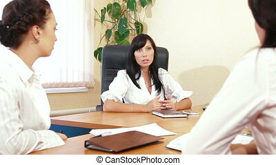 Discussing Business Issues - Three Young Women Discussing...