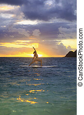 sunrise yoga on paddleboard - woman doing yoga on her paddle...