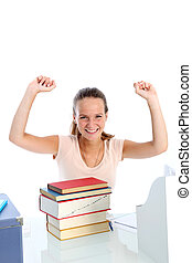 Jubilant young student sitting at her desk in front of a...