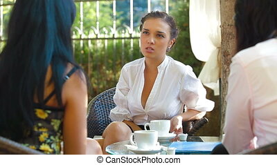 Gossip Time - Three female friends chat over a hot drink in...
