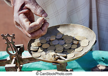 Moroccan Dirham coins. - Hand of a market vendor holding...