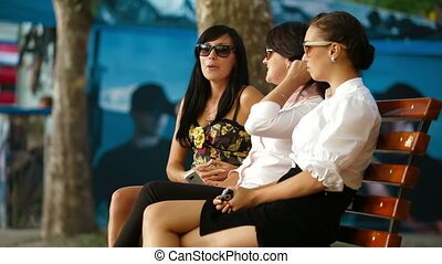 Women Conversation - Three female friends immersed in...